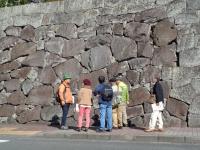 駿府城公園の石垣を巡り、石垣の前で観光ボランティアの説明を受ける参加者。