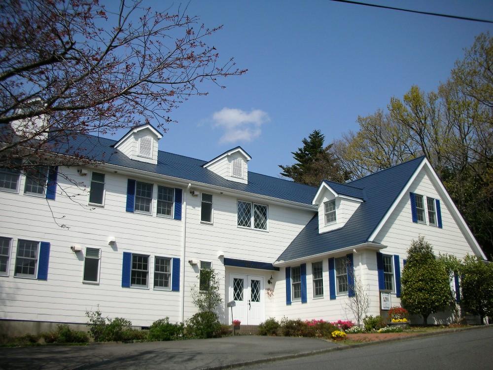 青空に映える紺色の屋根と白い壁のアメリカン・ハウス